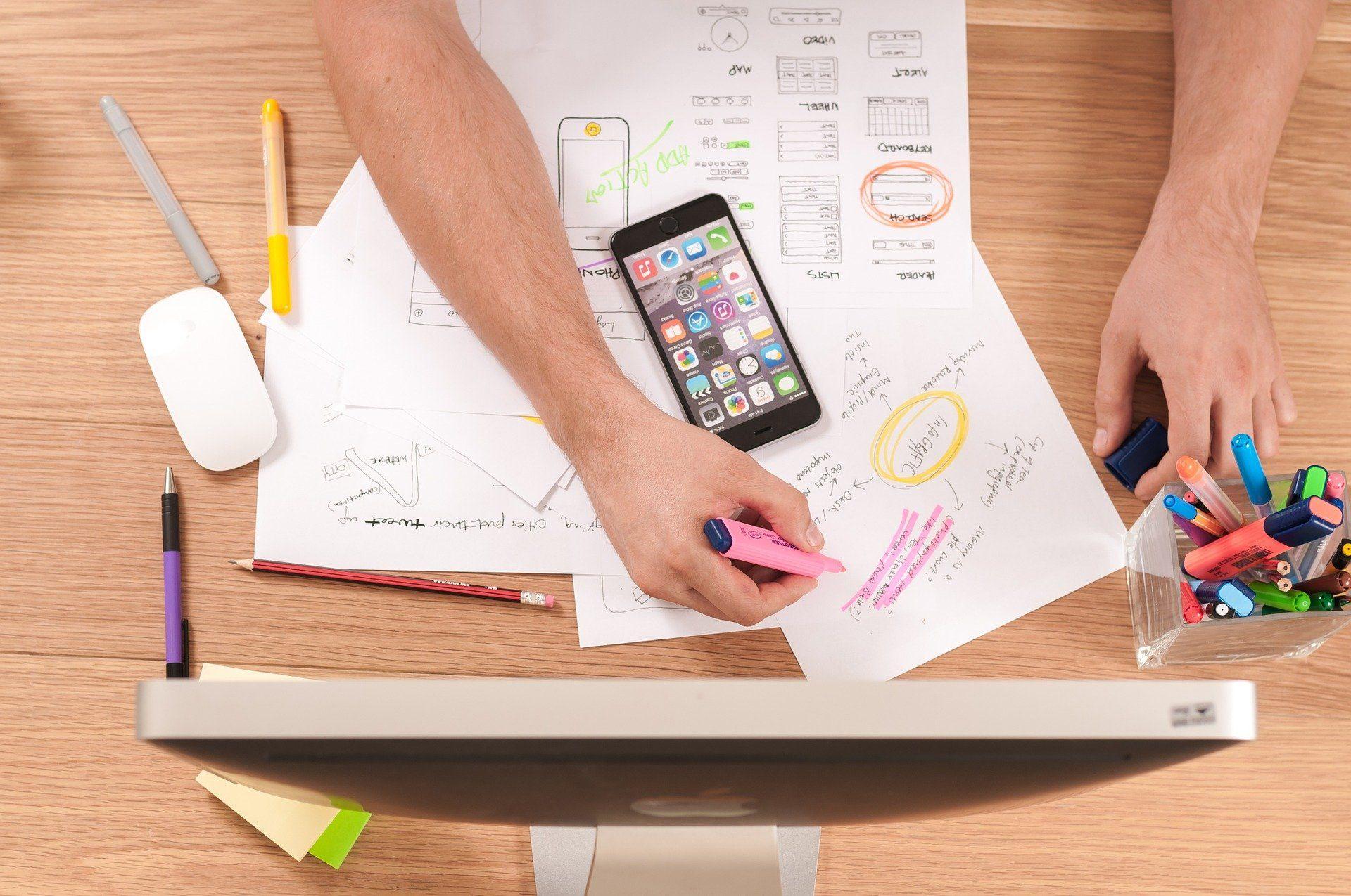 designer UX fazendo um rascunho do seu produto no papel, estando em frente o computador