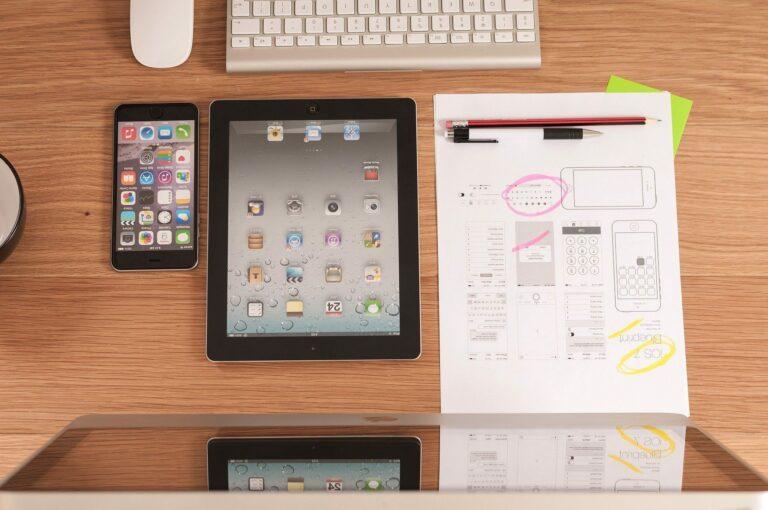 mesa com anotações, telefone, computador e tablet da Apple para serem usados no processo de construção da acessibilidade digital